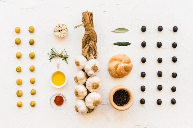 Plait of garlic with olives, bun and ingredients Free Photo