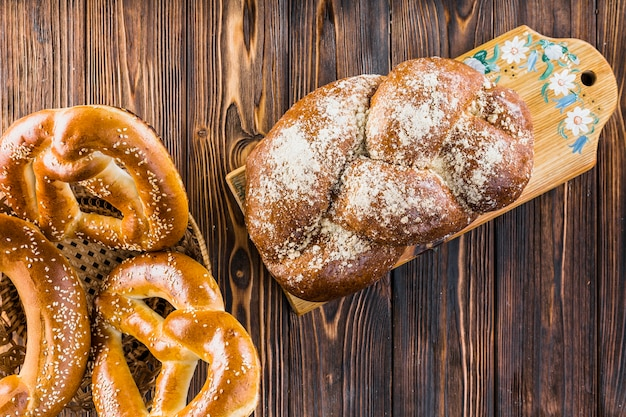 Plaited loaf on chopping board and pretzels in basket over the table Free Photo