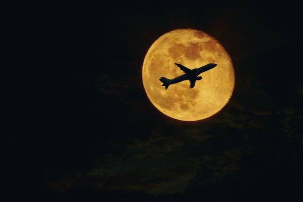 Plane, aircraft silhouette against full moon Premium Photo