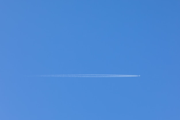 Plane flying through the clear blue sky overhead, with a trail behind it. Premium Photo