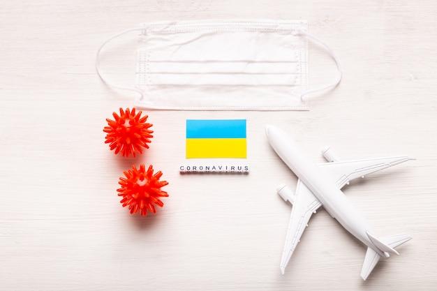 Модель самолета и маска для лица и флаг украины. коронавирус пандемия. запрет на полеты и закрытые границы для туристов и путешественников с коронавирусом ковид-19 из европы и азии. Premium Фотографии