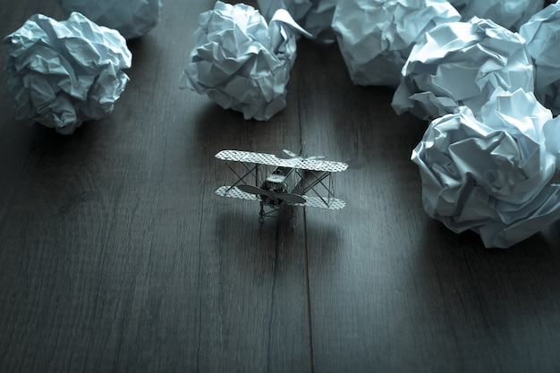 Plane model with crumpled paper on wood background. business frustrations, job stress and failed exam . Premium Photo