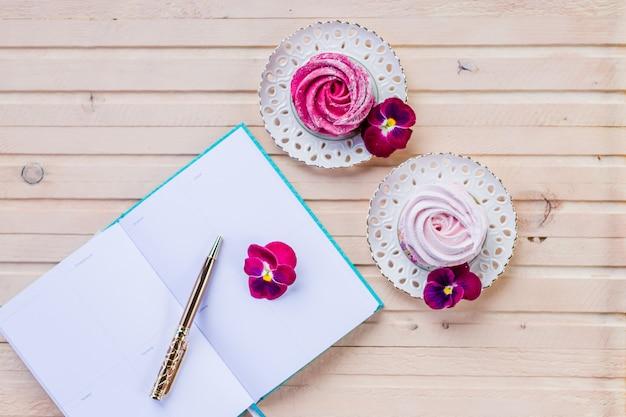紙の空白、ピンクの花、鉛筆でフェミニンなワークスペース。事業コンセプト。フラット横たわっていた、トップビュー。おはよう、planning.marshmallowと開かれた本。ロマンチックな瞬間。 Premium写真