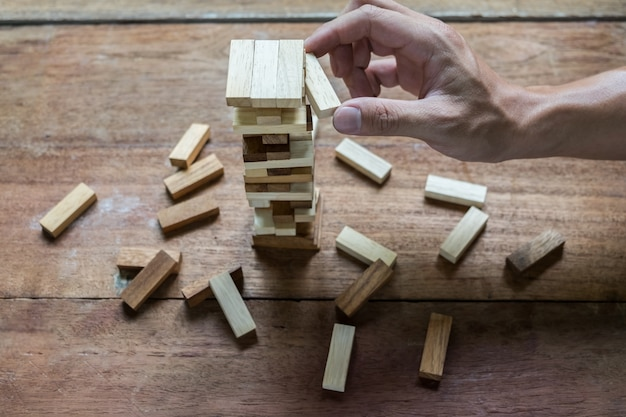 Planning, risk and strategy in business, businessman and engineer gambling placing wooden block on a tower. Free Photo