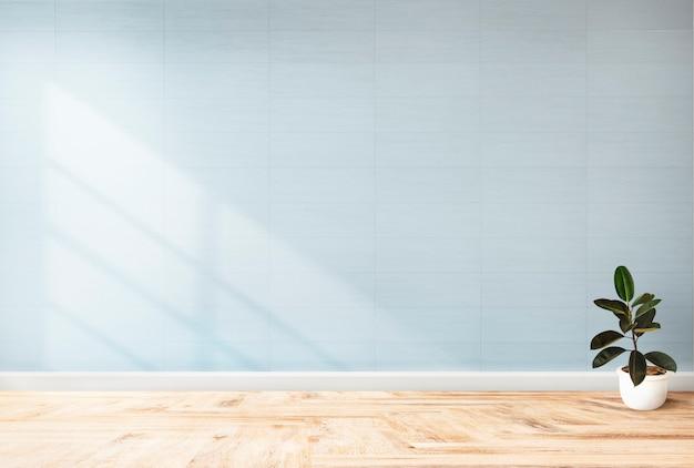 青い壁のモックアップに対して植える 無料写真