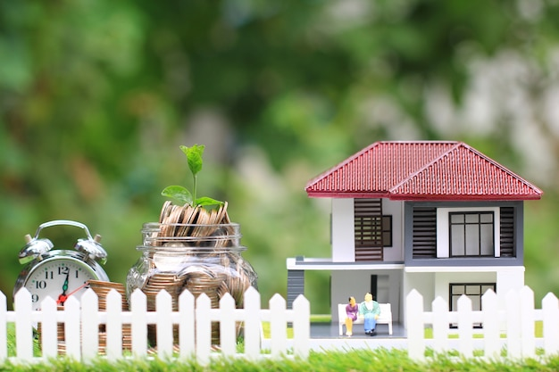 Plant growing on coins money in glass bottle with model house and miniature couple Premium Photo