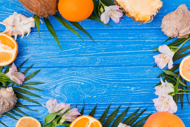 Plant leaves and fruits near flowers with seashells Free Photo