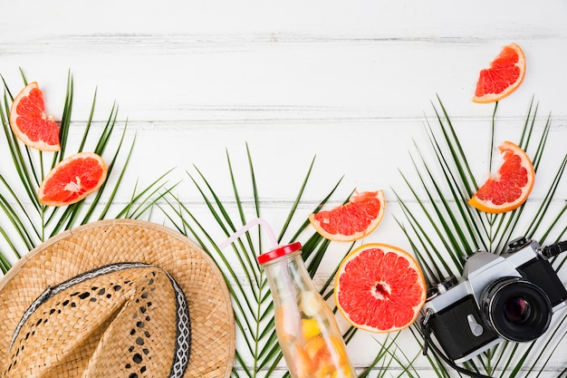 Plant leaves near citruses and hat with camera Free Photo