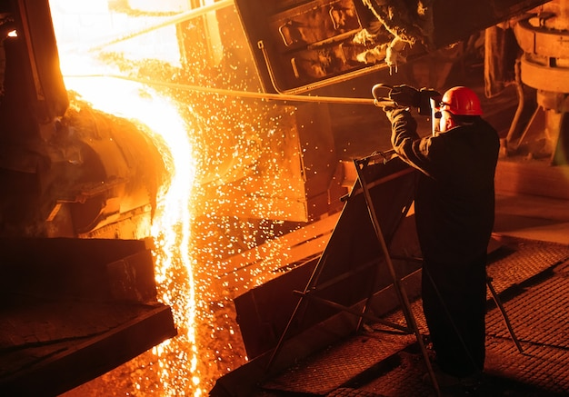 Plant for the production of steel. an electric melting furnace. factory worker takes a sample for metal. Premium Photo