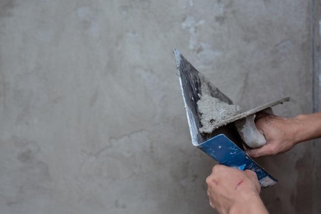 Plasterer renovating indoor walls. Free Photo
