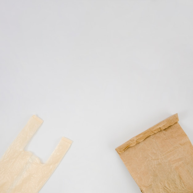 Plastic bag and brown paper bag with copy space white backdrop Free Photo