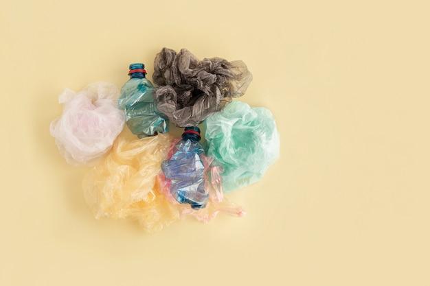 Пластиковые пакеты и бутылки на желтом. нет концепции пластикового мусора. Premium Фотографии