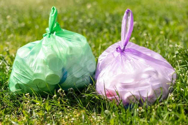 Sacchetti di plastica con rifiuti su erba Foto Gratuite