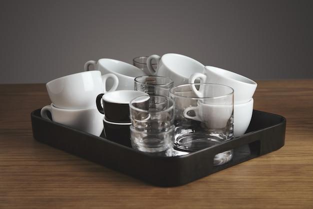 깨끗한 빈 흰색 커피, 차, 위스키 잔 및 컵과 플라스틱 검은 Salver. 카페가 게의 두꺼운 나무 테이블에. 회색 배경에 고립. 무료 사진