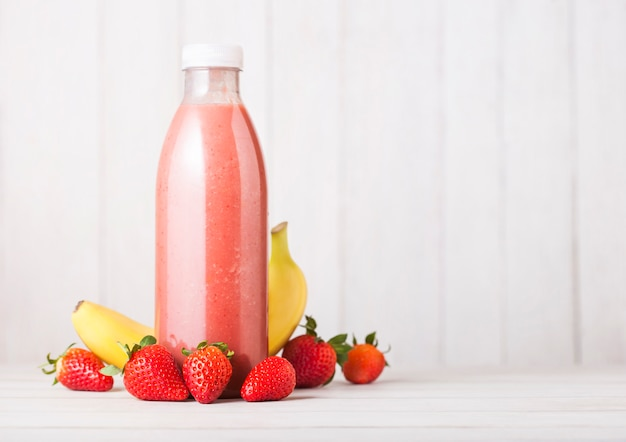 Plastic bottle with fresh summer berries smoothie on wooden table.strwberry and banana flavour. Premium Photo