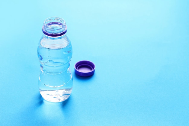 Plastic bottle with water on blue. Premium Photo
