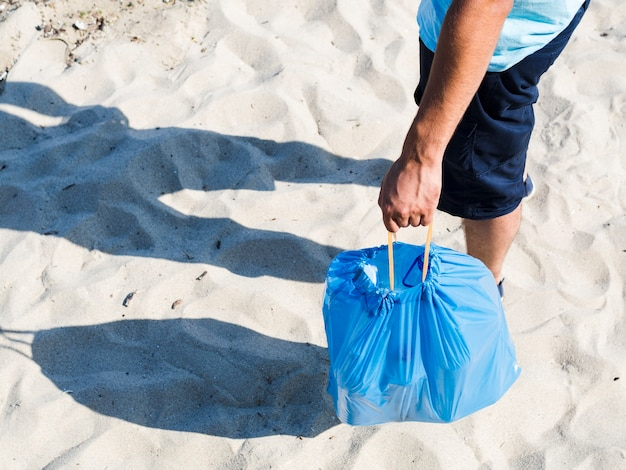 Plastic bottles in blue bag holding by man standing on sand Free Photo