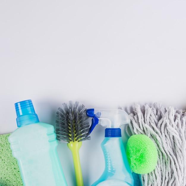 Plastic bottles brush, mop head and sponge on grey background Free Photo