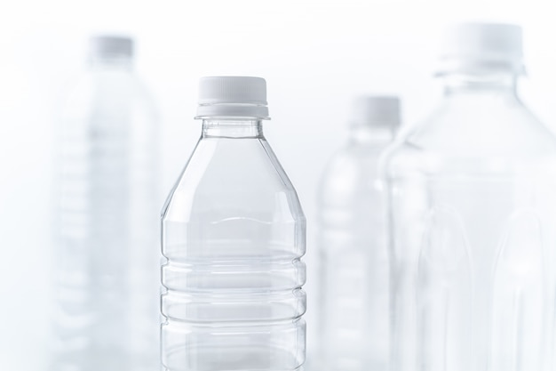 Plastic bottles in various shapes and sizes on white table and background Premium Photo