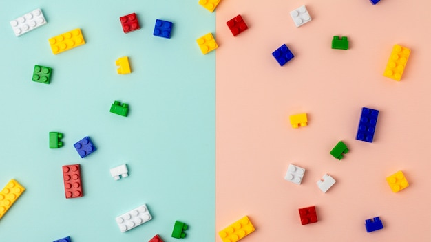 Plastic building blocks on blue and pink background Premium Photo