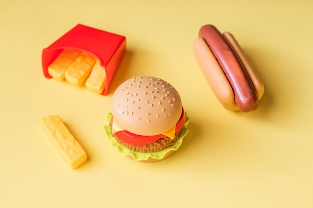 Plastic burger, salad, tomato, frying potatoes with a hot dog on a yellow background Premium Photo