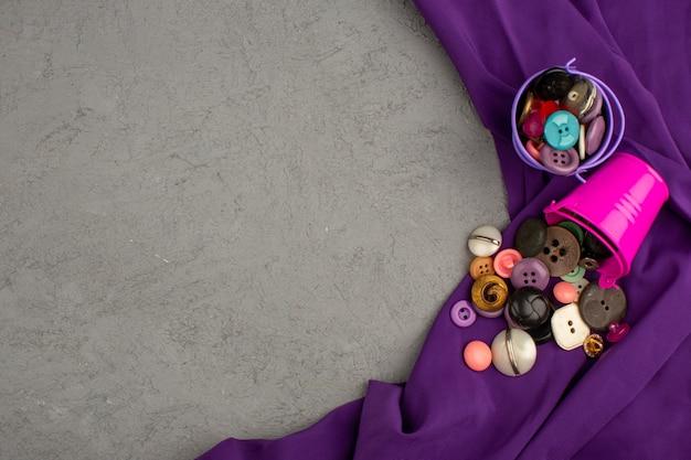紫色のティッシュと灰色の机の上の紫色とピンクの鍋の中のプラスチック製のボタンカラフルなヴィンテージ 無料写真