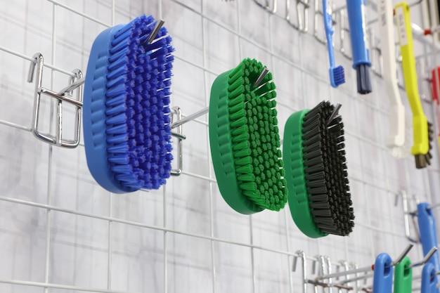 Plastic cleaning brushes in supermarket hanger ; Premium Photo