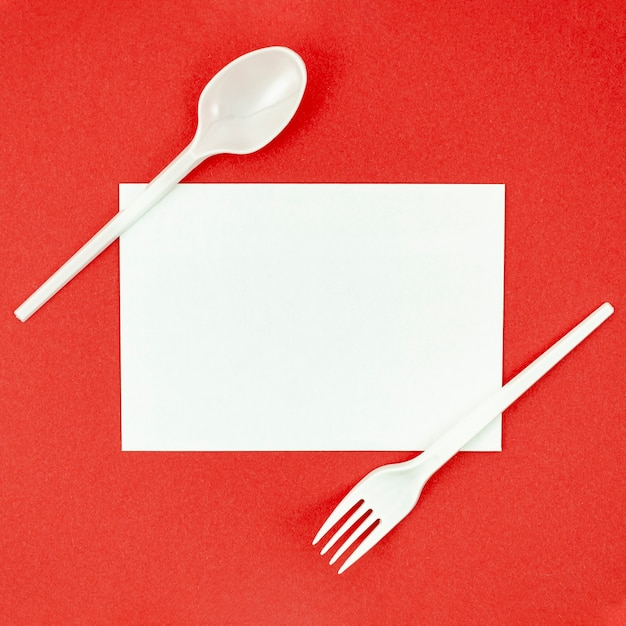 Plastic cutlery for picnics on red background Free Photo