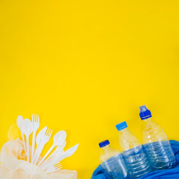 Plastic fork and spoon with empty plastic bottle in plastic bag over yellow backdrop Free Photo