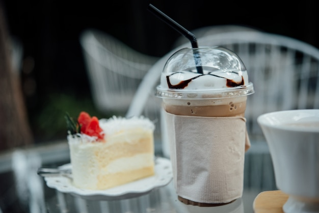 Plastic glass of iced coffee with cake on table in coffee shop Free Photo