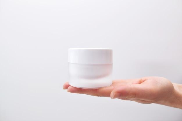 화이트 절연 여성 손에 크림의 플라스틱 항아리. 피부 젊음을 회복시키는 전문 화장품, 노화 방지 크림. 스킨 케어 개념. 프리미엄 사진