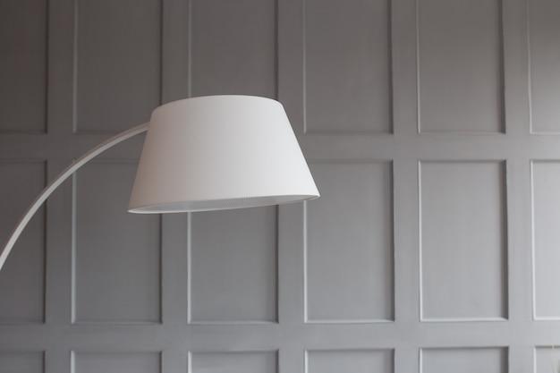 Пластиковая лампа в интерьере крупным планом. стена в стене серая. экологически чистый пластик. Premium Фотографии