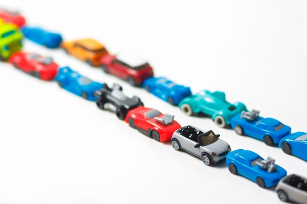 Plastic multi-colored toy cars are lined up on white   Premium Photo