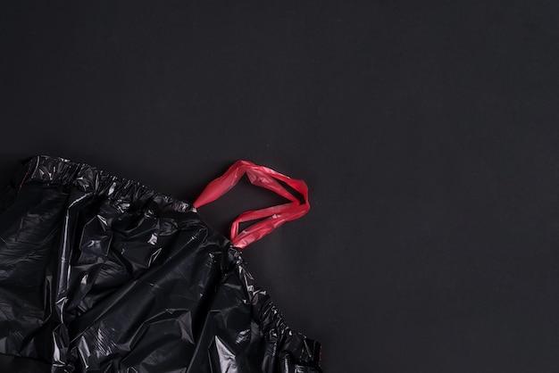 黒い背景にプラスチックの新しい空の使い捨てゴミ袋。上面図。 Premium写真