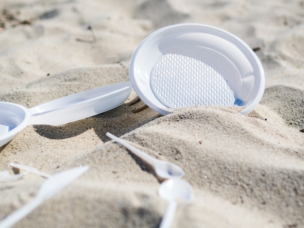 Plastic plate and spoon on beach sand Free Photo