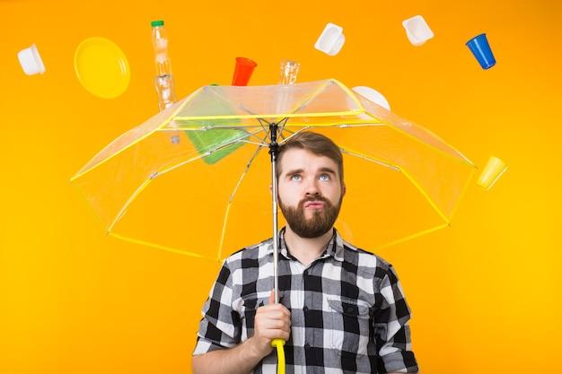 Проблема переработки пластика, концепция загрязнения и экологического бедствия - серьезный индийский мужчина думает об экологии под зонтиком на желтом фоне. Premium Фотографии
