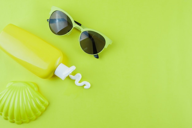 Plastic scallop; sunscreen lotion and sunglasses on green background Free Photo