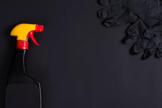 黒い背景にプラスチックスプレーボトルとゴム手袋。クリーニングのコンセプト Premium写真