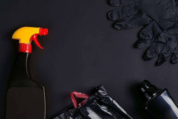 黒い背景にプラスチックスプレーボトル、ゴミ袋、ゴム手袋。 Premium写真