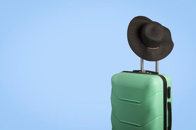 ホイールのプラスチックスーツケースと青色の背景のハンドルにつばの広い帽子。旅行の概念、休暇旅行、親戚への訪問 Premium写真