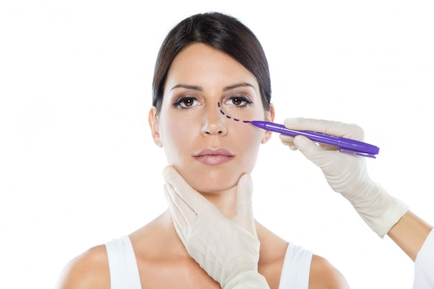 Plastic surgeon drawing dashed lines on her patient's face. Free Photo