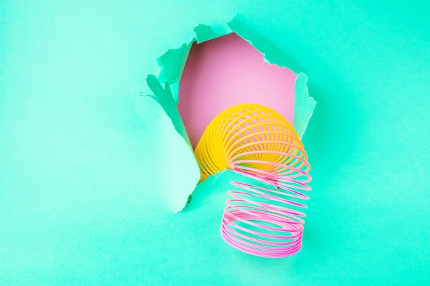 Plastic toy rainbow hanging from a hole of green paper. Premium Photo