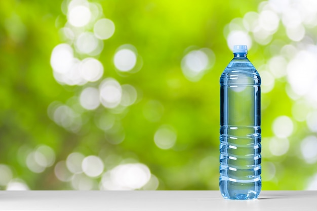 Plastic water bottle with blue cap on the wooden table Premium Photo