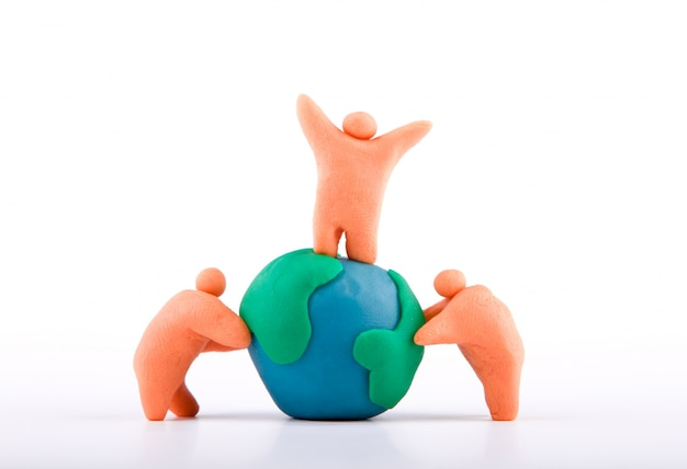 Plasticine of people embracing the earth Free Photo