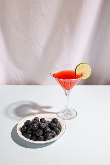 Plate of blue berries with cocktail beverage above white desk Free Photo
