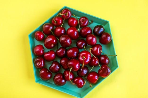 Plate of cherry on yellow background Premium Photo