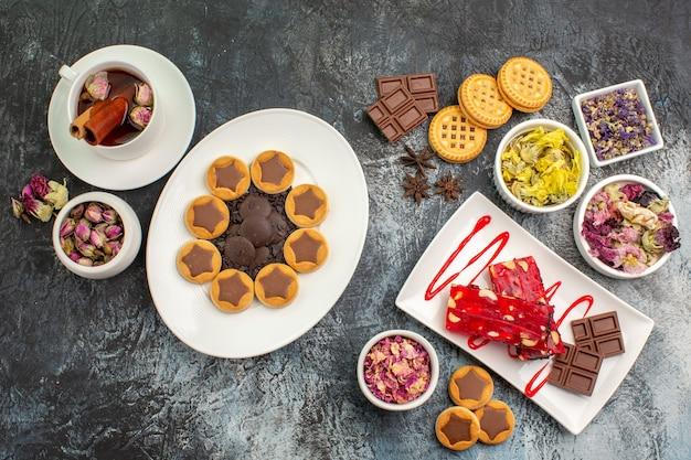 Un piatto di biscotti e cioccolato con una tazza di tisana e fiori secchi su grigio Foto Gratuite