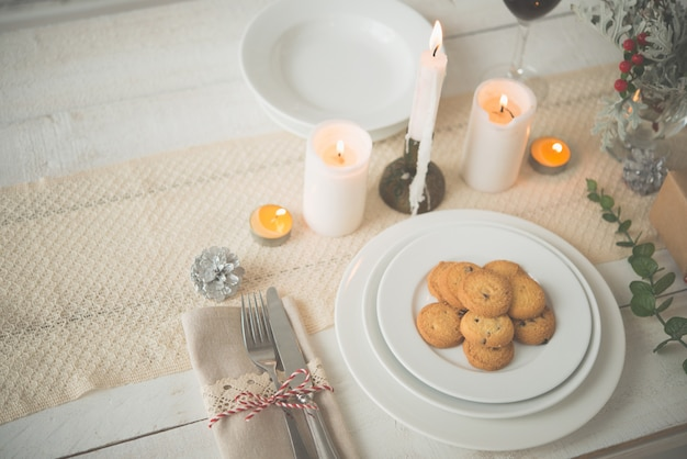 Plate of cookies on table set up for christmas dinner Free Photo