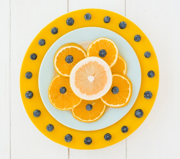 Plate decorated with blueberries and orange slices on wooden desk Free Photo