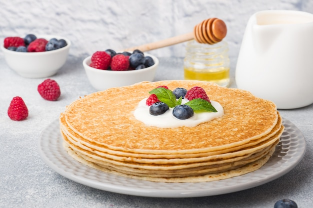 Plate of delicious thin pancakes with berries on grey table Premium Photo